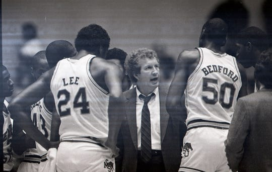 Former Memphis State basketball coach Dana Kirk, center, speaks to his players during a timeout in a game against Middle Tennessee State at Mid-South Coliseum on Dec. 5, 1984.