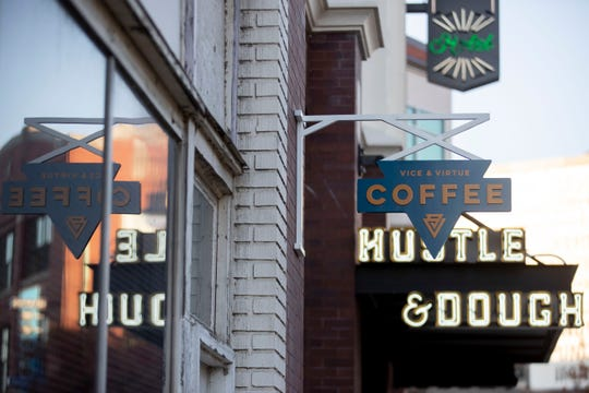 Signs for Vice & Virtue coffee and Hustle & Dough bakery face South Main Street on Tuesday, Nov. 5, 2019, at Arrive Memphis Hotel.
