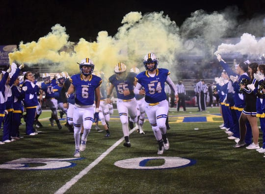 The Mountain Home Bombers run onto the field before a game last season at Bomber Stadium.