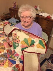 """Ozark County native Donna Walker, a 90-something """"fabric hound,"""" pieced her first hand-sewn quilt when she was 10 years old in 1937. Here, she holds a hand-pieced and hand-sewn Dresden plate quilt, one of many handmade quilts in her collection. This one, a family heirloom, is not included in the Historium display."""