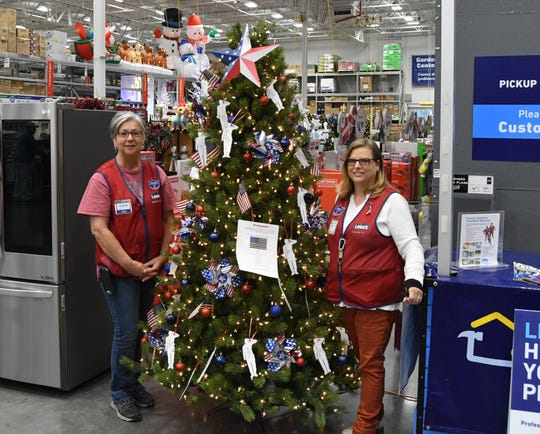 Lowe's employees Debbie Miller (left) and Pam Burns (right) stand next to the Veterans Tree currently out on the floor of the Mountain Home Lowe's.