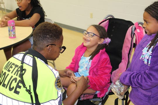 Layla Scott, center, with her sister, Hannah, and Sgt. Bonita Blue at the 2019 T.E.A.M. 1 summer camp for girls with special needs, a camp started by Officer Angela Booker with her own money, on her own time.