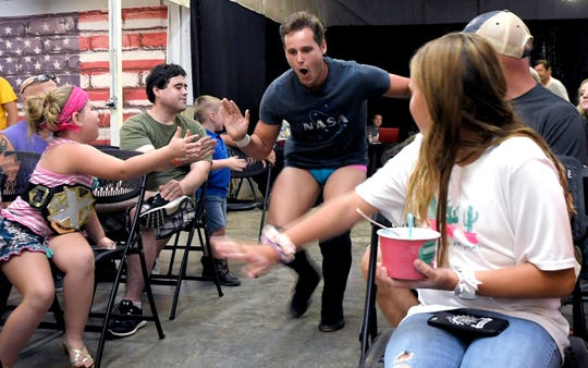 Wrestling fans welcome a USA Pro wrestler during a match at the Stables Event Center in Centerville, Tenn., on Aug. 17, 2019. The event center was once a walking horse stable and then a clothing factory before a lifelong resident bought the building and converted it into a community hub.