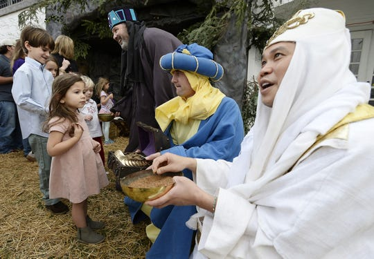 Dressed as the three wise men, Justin Gung, right, Phillip Harrison, center, and Tate Rich, top, talk with a group of children during the Walk Thru Bethlehem reenactment at the Woodmont Christian Church Dec. 13, 2015 in Nashville, Tenn.