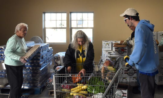 Food pantry volunteers Dot Ehlermann and Paulette Painter offer carrots and yogurt to fellow volunteer Donnie Urban at produce market on Tuesday, Oct. 29, 2019, at the Food Pantry Network of Licking County on Brice Street in Newark. Urban filled the cart for a visitor who was unable to come in to the market themselves.