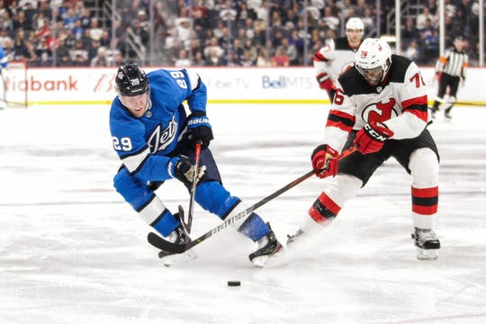 New Jersey Devils defenseman P.K. Subban (76) and Winnipeg Jets forward Patrik Laine (29) battle for the puck during the second period at Bell MTS Place.