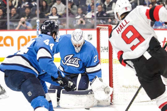 Winnipeg Jets goalie Connor Hellebuyck (37) makes a save on a shot by New Jersey Devils forward Taylor Hall (9) during the first period at Bell MTS Place.