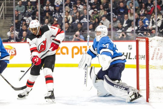 New Jersey Devils forward Wayne Simmonds (17) attempts to deflect the puck past Winnipeg Jets goalie Connor Hellebuyck (37) during the first period at Bell MTS Place.