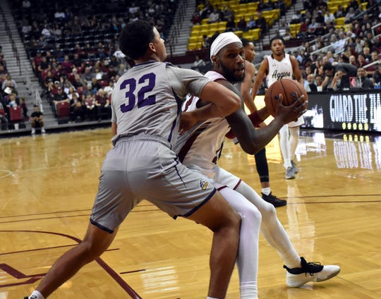 C.J. Bobbitt gets ready to make a spin move near the basket against a Mustang defender as NMSU took on WNMU at the Pan Am on Tuesday night.  Photo taken 11/5/19.