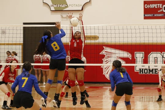Loving's Andriva Gomez blocks a Jal spike attempt in the first set of Tuesday's district tournament game on Nov. 5, 2019. Loving swept Jal, 25-10, 25-5, 25-16.