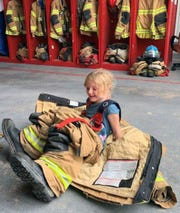 A child tries on bunker gear in the WIPP Fire Station.