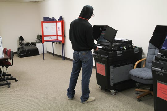 A poll worker casts his vote at the Lincoln County Courthouse voting center in Carrizozo, NM on Tuesday, Nov. 5.