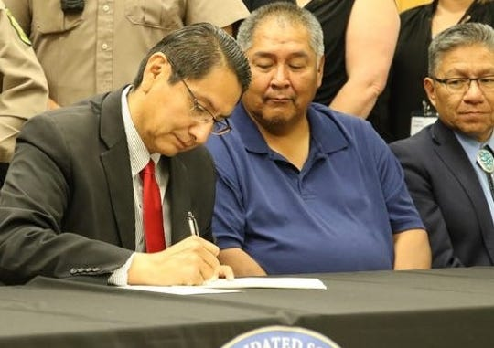 Central Consolidated School District Board of Education President Charlie Jones Jr., center, watches Navajo Nation President Jonathan Nez sign the agreement between the school district and the tribe for school resources officers on Aug. 26 in Shiprock.