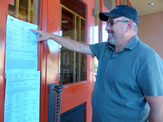 Lincoln County Commissioner Dallas Draper checks out the lengthy ballot for the nonpartisan election Tuesday.