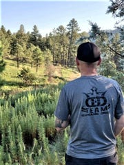 A disc golf players takes a look at the course on moon Mountain.