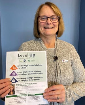 Jean Ivory of the Birmingham Branch of the American Association of University Women showss the poster featuring the Nov. 15 Levels Up Conference for women, which will provide information about GED programs, college programs, apprenticeships, scholarships and other aspects of improving educational status and employability.