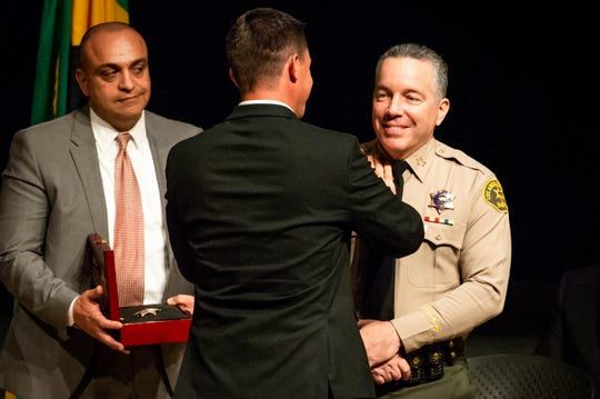 Critics accused Los Angeles Sheriff Alex Villanueva, right, of tolerating domestic violence when he reinstated Deputy Caren Carl Mandoyan, left,  to the force. Mandoyan had been fired by Villanueva's predecessor after an internal probe found him culpable of domestic abuse.