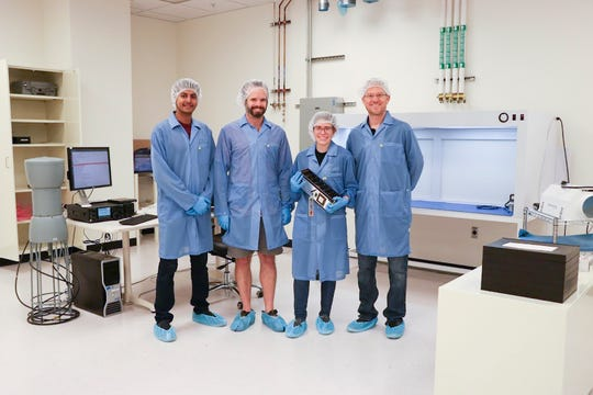 From left to right, student Vivek Chacko, Assistant Professor Danny Jacobs, student Sarah Rogers, and Professor Judd Bowman pose with the Phoenix spacecraft at Arizona State University before the satellite was delivered to be launched into space.