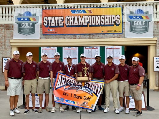 Nov. 5, 2019; Hamilton boys golf team holds its state championship trophy at Omni Tucson National golf course.