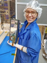 Student Sarah Rogers holds the miniature satellite Phoenix, which she and other students built at Arizona State University.