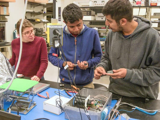 Students Sarah Rogers, Vivek Chacko and Raj Biswas discuss testing an electrical interface board for the Phoenix CubeSat in a lab at Arizona State University.