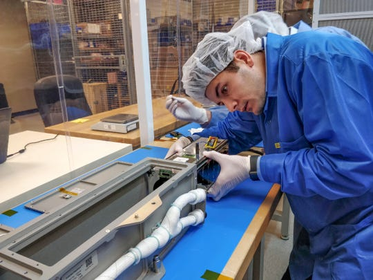 Mission manager Jake Cornish of the company Nanoracks checks that the Phoenix CubeSat, which was built by students at Arizona State University, is sized correctly to be deployed from the International Space Station.
