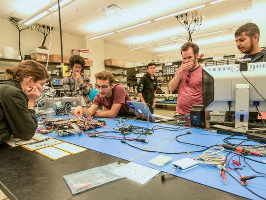 Working in a lab at Arizona State University, students discuss how satellite components will connect with each other.