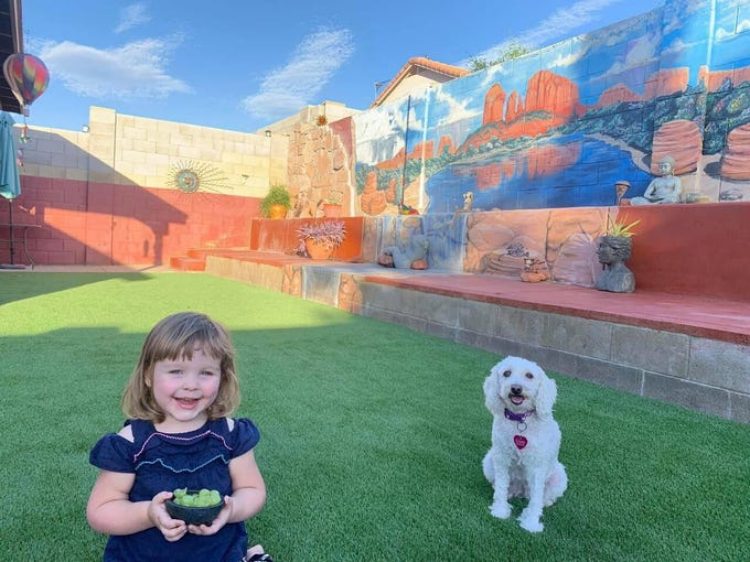 Denette Dunn's granddaughter Ella and her pup Coco in the backyard.