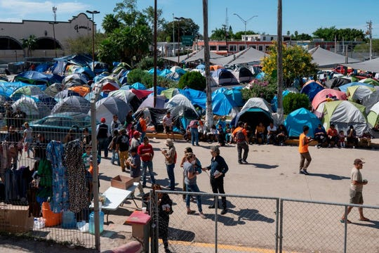 Migrantes en espera de proceso de asilo esperan en Tijuana.