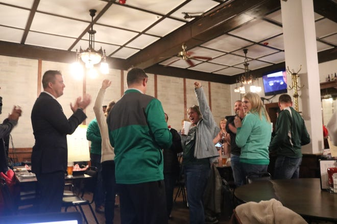 Guy Parmigian, left, superintendent of Benton-Carroll-Salem Schools, Treasurer Cajon Keeton and other supporters gather results as they came in after polls closed on Tuesday night at The Hartford House Restaurant in downtown Oak Harbor.
