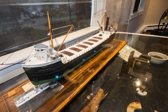 A model of the Regina sits on top of a display case holding artifacts brought back from the ship.