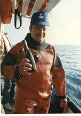 Wayne Brusate, a commercial diver, holds up a bottle of champagne found among the remnants of the sunken SS Regina in the mid-1980s.