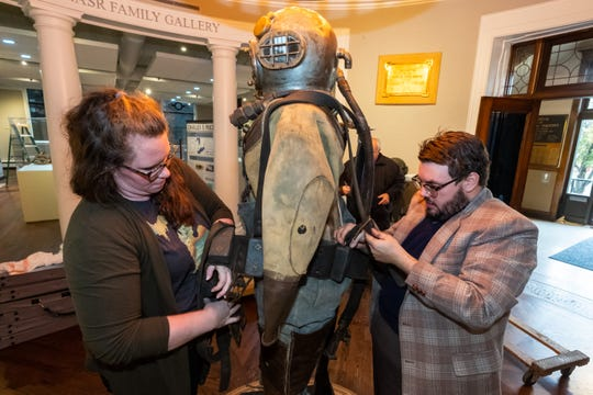 Port Huron Museums Executive Director Veronica Campbell, left, and Manager of Community Engagement Andrew Kercher work to set up a diving suit from 1913 that will be on-display as part of the museum's new exhibit Wednesday, Nov. 6, 2019, in the museum's Carnegie Center.
