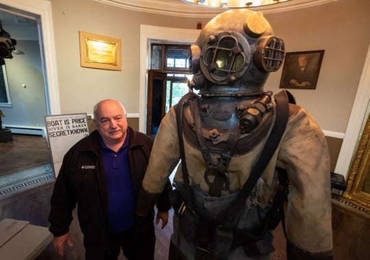 Wayne Brusate stands next to a diving suit from 1913 on-display in the Port Huron Museum's new exhibit Wednesday, Nov. 6, 2019, in the museum's Carnegie Center.