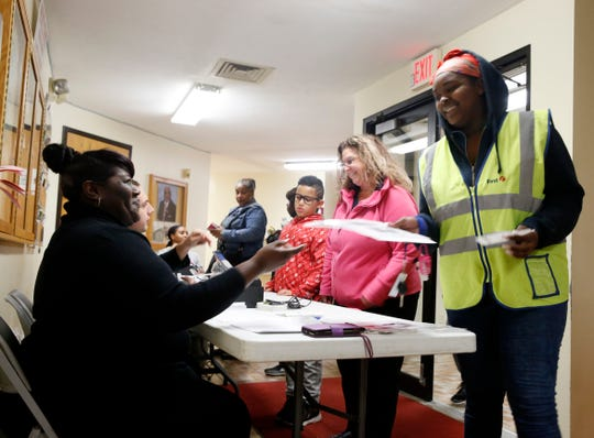 Davanesha Higgs receives her ballot from Charlene Bennermon at Beulah Baptist Church on November 5, 2019. This is the first election Davanesha has voted in.