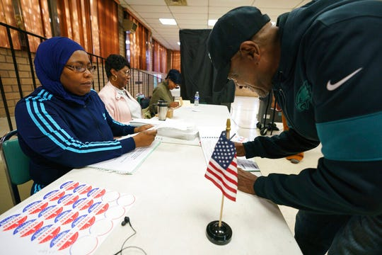 Ora Henry, left, signs in Otis Graham, right, as he votes on Election Day at Zion Baptist Church Of Philadelphia in Philadelphia, Tuesday, Nov. 5, 2019. (Jessica Griffin/The Philadelphia Inquirer via AP)