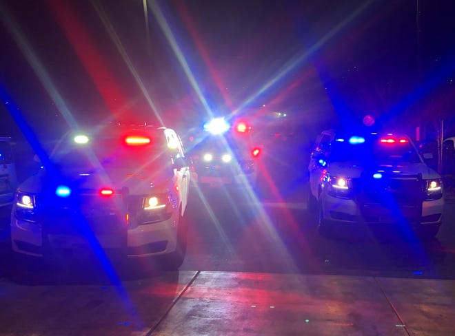 A photo showing three Washoe County Sheriff's patrol vehicles with flashing lights. The sheriff is investigating a body found in a burning car off Pyramid Highway north of Sparks.