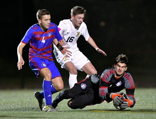Fairport goalie Michael Nesser, right, dives on a loose ball in front of Timmy Hirschler, left, and McQuaid's Ryan Brown during the Class AA sectional final at Spencerport High School, Tuesday, Nov. 5, 2019. No. 1 seed Fairport and No.2 seed McQuaid were named Class AA co-champions after playing to a 1-1 draw. Fairport advanced to the Western Regional on penalty kicks (6-5).