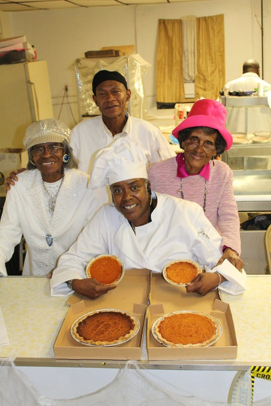 Victoria Lang holds the main attraction at The Sweet Potato Pie Place. Behind her, left to right, are Bertha Smith Israel, Dennis Lang and Gladys Burke.