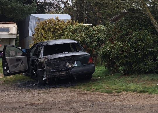 A burned vehicle sits at a home in the 11000 block of Causey Lane SE near Sublimity. A man is in custody on charges of arson after the incident.
