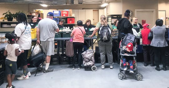 People pick up produce, canned goods, meat, dairy and bread at the River City Food Bank in Sacramento.
