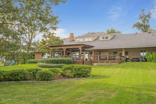 The home is situated on two acres with mature trees and water views.