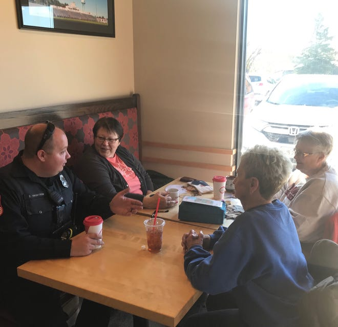 Brandon Police officer Zachary Hagstrom, left, talks with customers during Brandon's Coffee with a Cop event at Scooter's on Thursday, Oct. 31.