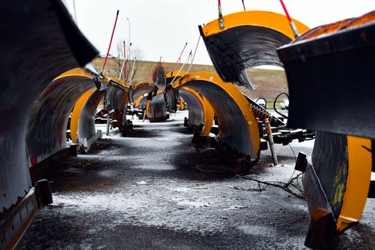 Snowplow blades rest in a line as snow and frozen rain falls  on Wednesday, November 6, at Sioux Falls Fleet Management.