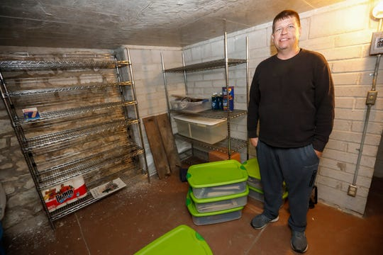 Justin Baker stands inside the bomb shelter located in his childhood home on East Walnut Street on Wednesday, Nov. 6, 2019.