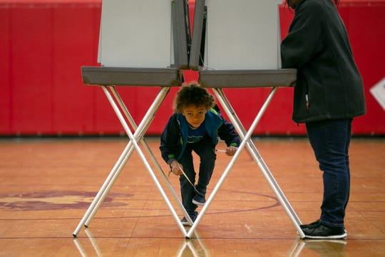 Declan Brady peeks under the voting booth while his grandmother Darlene Walker votes at Drew Middle School on Election Day in Stafford, Va., Tuesday, Nov. 5, 2019.