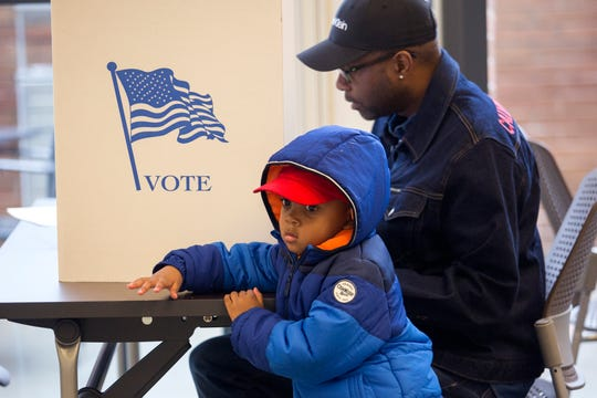 Asher Artis, 3, waits for his grandfather, Keith Smith, to finish filling out his ballot at The Kroc Center Hampton Roads, a polling location in Norfolk, Va., on Tuesday, Nov. 5, 2019.