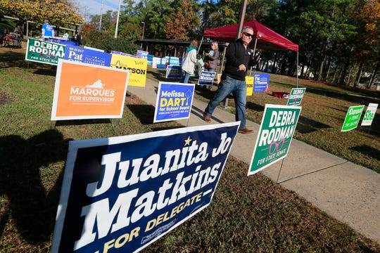 Voters walk through a sea of campaign signs at a polling station in Richmond, Va., Tuesday, Nov. 5, 2019. All seats in the Virginia House of Delegates and State senate are up for election.