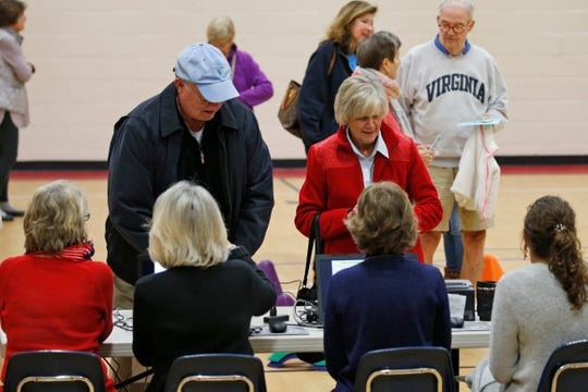 Voters line up to get ballots at a polling station in Richmond, Va., Tuesday, Nov. 5, 2019. All seats in the Virginia House of Delegates and State senate are up for election.