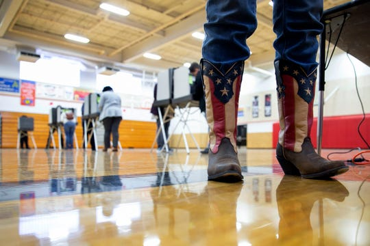 Chief Election Official Sandy Pace wears her patriotic-themed boots while staffing the polling station at Drew Middle School on Election Day in Stafford, Va., Tuesday, Nov. 5, 2019.